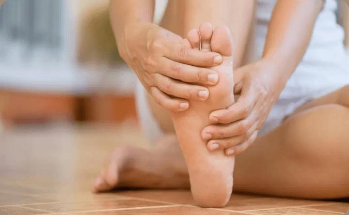 Woman massaging her plantar fasciitis pains