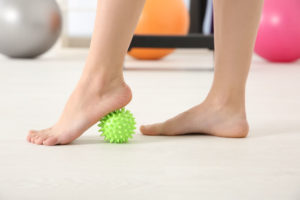 A pair of flat feet exercising with a ball
