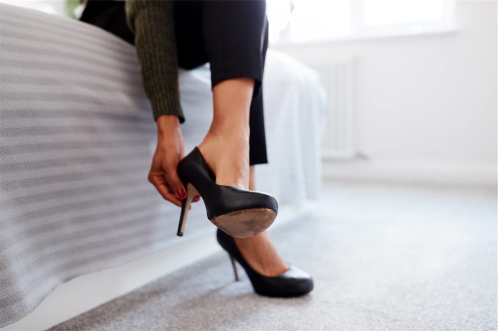 Woman with a flat foot wearing black high heels