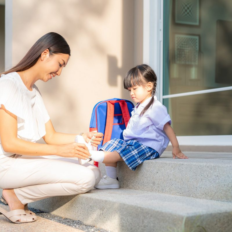 Asian mother helping her daughter put shoes on or take off at outdoor park getting ready to go out together or coming back home from school in happy family with kids concept.